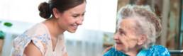 Junge Frau im Gespräch mit Seniorin