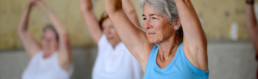 Seniorin macht Gymnastik mit Armen über dem Kopf